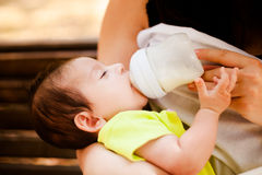 The image of the woman feeding her baby from a children's small bottle Stock Images