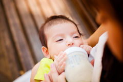 The image of the woman feeding her baby from a children's small bottle Stock Image
