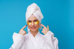 Image of woman with gel pads under eyes and towel on her head. On empty blue background stock image