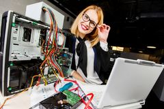 Image of woman in glasses at table with broken processor and laptop. In office stock photo