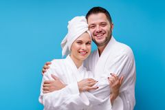 Image of woman and man in bathrobe hugging themselves. Image of women and men in bathrobe hugging themselves on empty blue background stock images