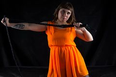 Image of woman in orange dress with whip Stock Images