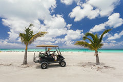 Image of woman riding a golf cart on the beach. Stock Photography