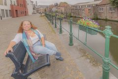 Image of a woman sitting on a bench next to a canal in the city of Ghent. Belgium on a day touring enjoying the city royalty free stock photography