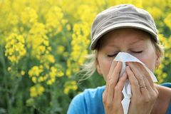 Woman sneezing because of  allergy to pollen. Image of a woman sneezing because of  allergy to pollen Royalty Free Stock Photography