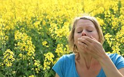 Woman sneezing because of  allergy to pollen. Image of a woman sneezing because of  allergy to pollen Stock Image