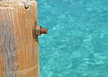 Image of the wood, the bolt, nut in the pier at sea . Royalty Free Stock Photo