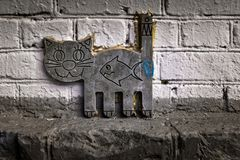 Image of a wood cat on a white brick wall royalty free stock photos