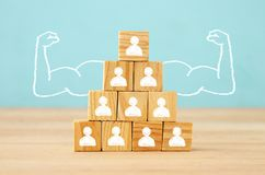Image of wooden blocks with people icons over table ,building a strong team, human resources and management concept. Royalty Free Stock Photography