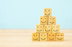 Image of wooden blocks with smiling faces icons over table ,building a strong team, human resources and management concept. Image of wooden blocks with smiling stock photography