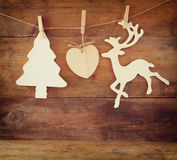 Image of wooden decorative christmas tree and reindeer hanging on a rope over wooden background. Stock Images