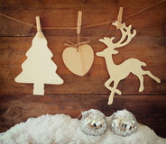 Image of wooden decorative christmas tree and reindeer hanging on a rope over wooden background. Stock Photos