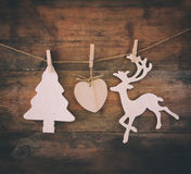 Image of wooden decorative christmas tree and reindeer hanging on a rope over wooden background Royalty Free Stock Photo