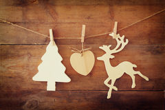 Image of wooden decorative christmas tree and reindeer hanging on a rope over wooden background Royalty Free Stock Photography
