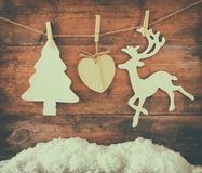 Image of wooden decorative christmas tree and reindeer hanging on a rope over wooden background Royalty Free Stock Photos