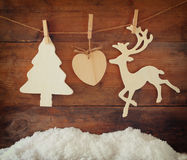 Image of wooden decorative christmas tree and reindeer hanging on a rope over wooden background Stock Photos
