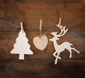 Image of wooden decorative christmas tree and reindeer hanging on a rope over wooden background Stock Photo