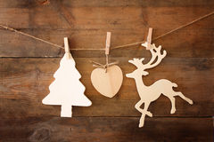 Image of wooden decorative christmas tree and reindeer hanging on a rope over wooden background Stock Photography