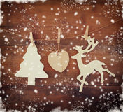 Image of wooden decorative christmas tree and reindeer hanging on a rope over wooden background with abstract snow overlay Royalty Free Stock Images