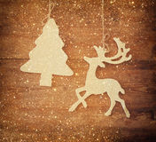 Image of wooden decorative christmas tree and reindeer hanging on a rope over wooden background with glitter overlay. Royalty Free Stock Photo
