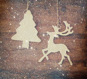 Image of wooden decorative christmas tree and reindeer hanging on a rope over wooden background with glitter overlay Royalty Free Stock Photography