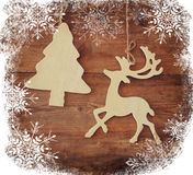 Image of wooden decorative christmas tree and reindeer hanging on a rope over wooden background with snowflake overlay. Royalty Free Stock Photography
