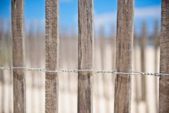 A wooden fence wrapped in wire at the beach to prevent erosion. An image of a wooden fence held together by wire erected at the beach to prevent erosion.  There Royalty Free Stock Photography