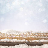 Image of wooden old table and december fresh snow on top. in front of glitter background. selective focus Royalty Free Stock Photos