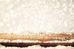 Image of wooden old table and december fresh snow on top. in front of glitter background. selective focus Stock Photos