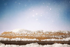 Image of wooden old table and december fresh snow on top. in front of glitter background. selective focus Royalty Free Stock Images