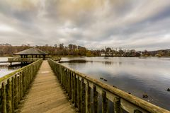 Image of a wooden path leading to a gazebo in the middle of the Doyards lake stock images