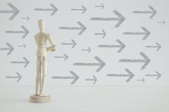 Image of wooden person standing with his back in front of textured background full of arrows pointing in same directions Stock Image