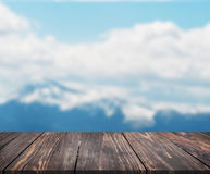 Image of wooden table in front of abstract blurred background of mountain. can be used for display or montage your products. Mock. Up for display of product stock photos