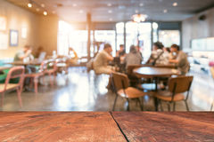 image of wooden table in front of abstract blurred background of restaurant