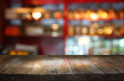 Image of wooden table in front of abstract blurred background of restaurant lights.  Royalty Free Stock Photography