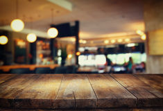 Image of wooden table in front of abstract blurred background of restaurant lights.  Stock Images
