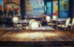 Image of wooden table in front of abstract blurred background of restaurant lights.  Stock Photo