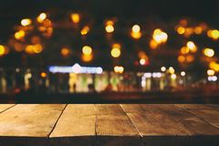 Image of wooden table in front of abstract blurred restaurant lights background Royalty Free Stock Photo