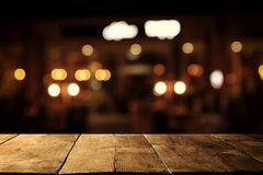 Image of wooden table in front of abstract blurred restaurant lights background. Image of wooden table in front of abstract blurred restaurant lights background Royalty Free Stock Images