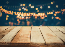 Image of wooden table in front of abstract blurred restaurant lights background.  royalty free stock photography
