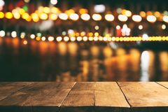 Image of wooden table in front of abstract blurred restaurant lights background. Royalty Free Stock Photo