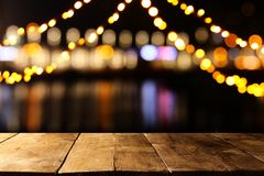 Image of wooden table in front of abstract blurred restaurant lights background. Image of wooden table in front of abstract blurred restaurant lights background Royalty Free Stock Photography
