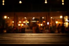 Image of wooden table in front of abstract blurred restaurant lights background. Image of wooden table in front of abstract blurred restaurant lights background Stock Image