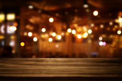 Image of wooden table in front of abstract blurred restaurant lights background Royalty Free Stock Photos