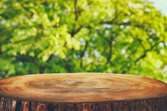image of wooden table in front green forest trees landscape background. for product display and presentation Royalty Free Stock Photo