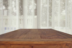 image of wooden table in front white curtains Stock Photo