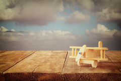 Image of wooden toy airplane over wooden table against cloudy sky. retro style image Stock Photo