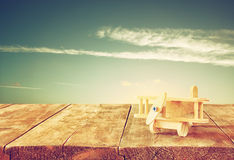 Image of wooden toy airplane over wooden table against sunset sky. retro style image Royalty Free Stock Photo