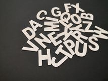 Closeup image of wooden white alphabet letters with black color background. royalty free stock photography