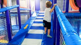 Image of 3 years old toddler boy climbing and crawling on the children palyground in shopping mall. There are lots of. Photo of 3 years old toddler boy climbing royalty free stock images